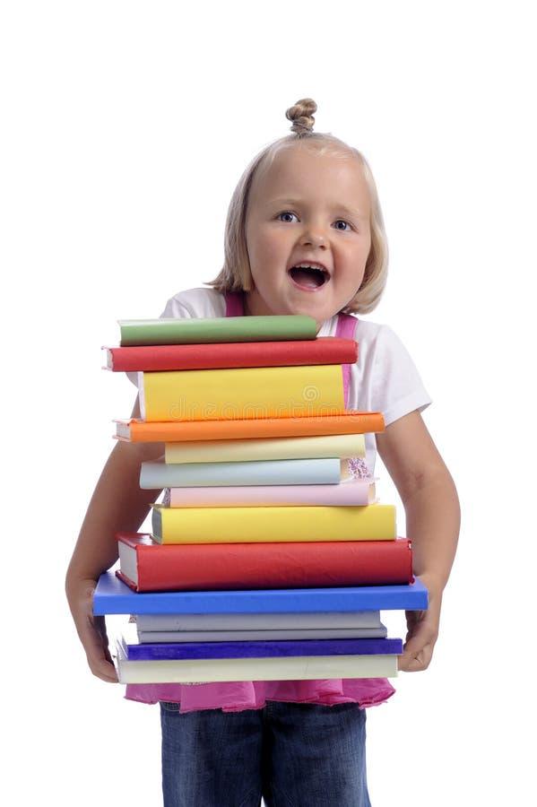Bambina felice con la pila pesante di libri fotografia stock