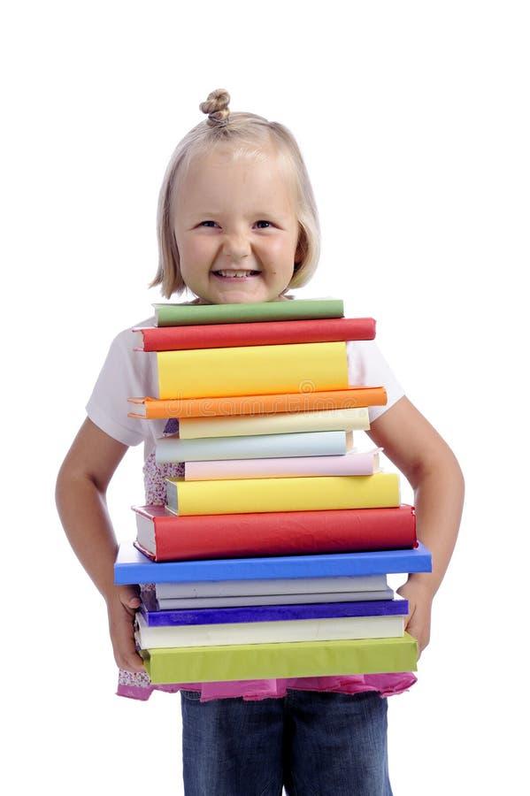 Bambina felice con la pila pesante di libri fotografie stock libere da diritti