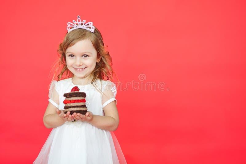 Bambina felice con la torta di compleanno isolata su fondo rosso fotografia stock