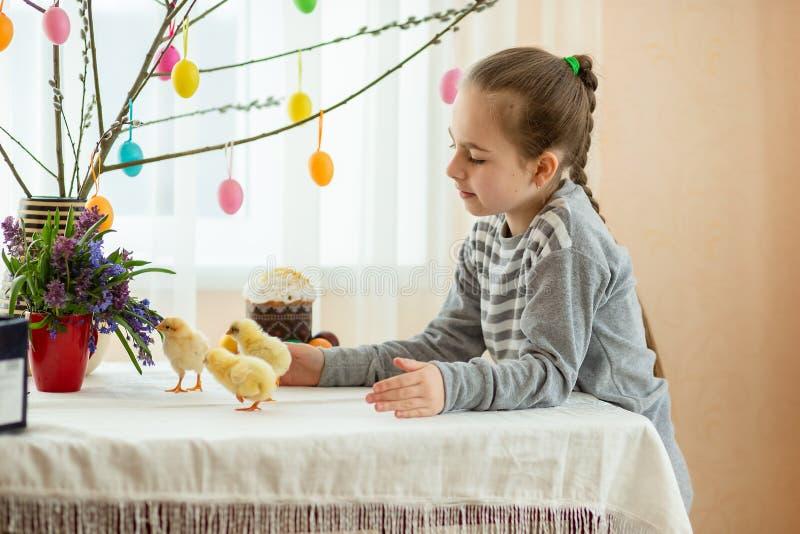 Bambina felice con pochi polli sul fondo della decorazione di pasqua fotografia stock