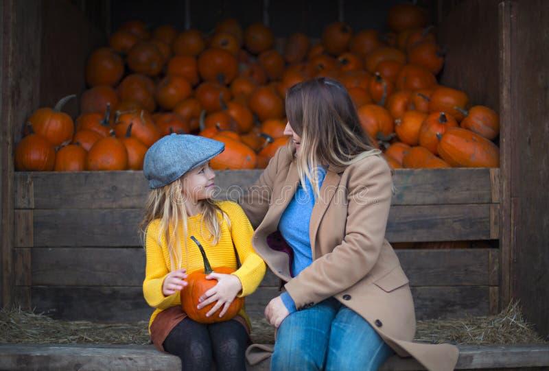 Bambina felice con sua madre ai precedenti della toppa della zucca di autunno fotografia stock libera da diritti
