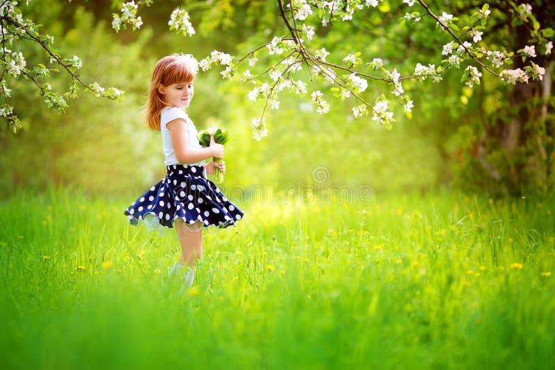 Bambina felice con un mazzo dei mughetti che hanno fotografia stock libera da diritti