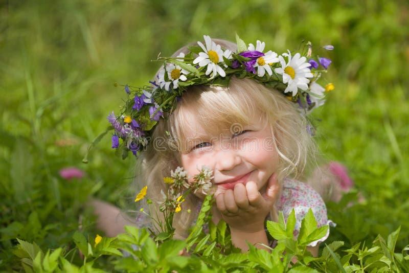 Bambina felice in corona dei fiori fotografia stock libera da diritti