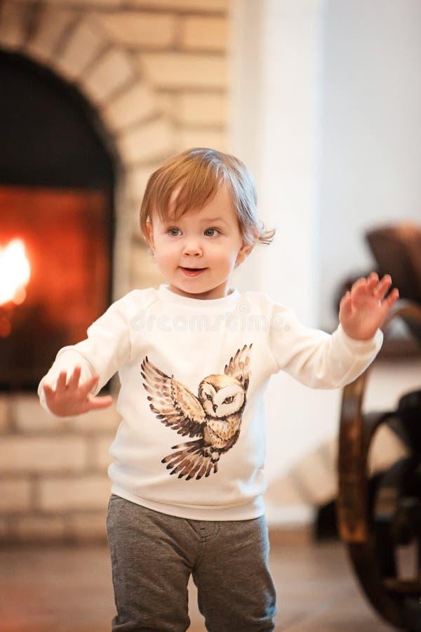 Bambina felice del bambino che sta a casa contro il camino immagine stock libera da diritti