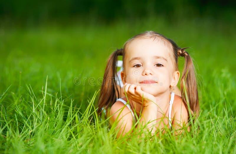 Bambina felice del bambino in vestito bianco che si trova sull'estate dell'erba immagine stock