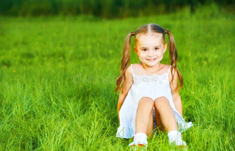 Bambina felice del bambino in vestito bianco che si trova sull'estate dell'erba fotografie stock
