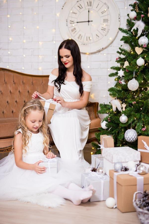 Bambina felice ed i suoi regali d'apertura di natale della madre in livi fotografie stock libere da diritti