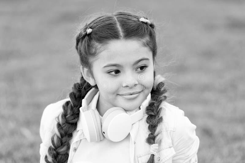 Bambina felice La bambina ascolta musica Bambino in cuffia avricolare Il bambino alla moda si rilassa su erba verde Umore della s fotografia stock