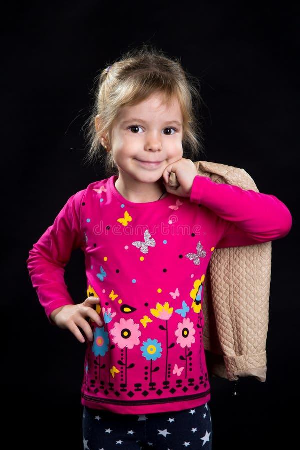 Bambina felice, modello con un rivestimento sulla spalla Fondo nero, foto dello studio fotografie stock libere da diritti