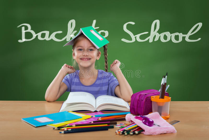 Bambina felice nel banco della scuola, dietro di nuovo al segno della scuola sulla lavagna immagini stock libere da diritti