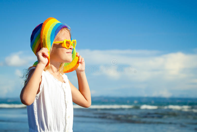 Bambina felice nel cappello che sta sulla spiaggia nel giorno t immagini stock