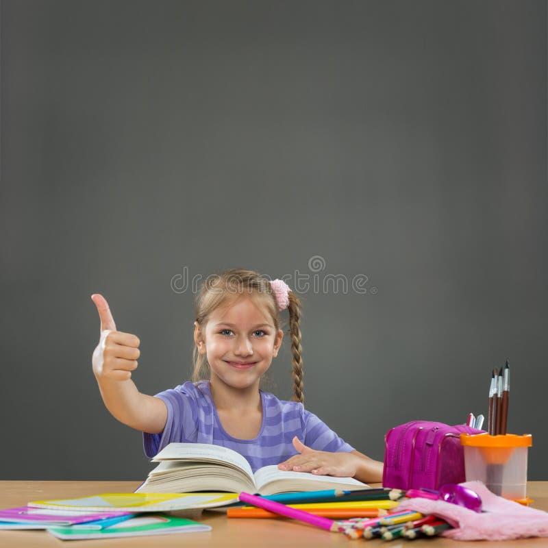 Bambina felice nelle manifestazioni di banco della scuola tutto il okay fotografie stock