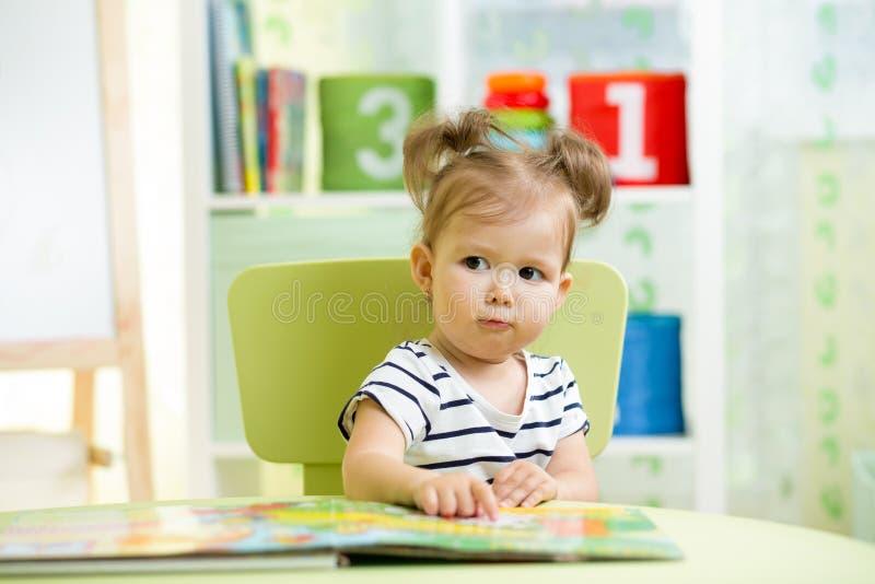 Bambina felice sveglia che legge un libro fotografia stock libera da diritti