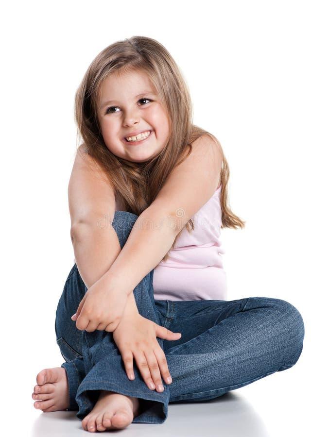 Bambina felice sveglia che si siede sulla priorità bassa bianca fotografia stock libera da diritti