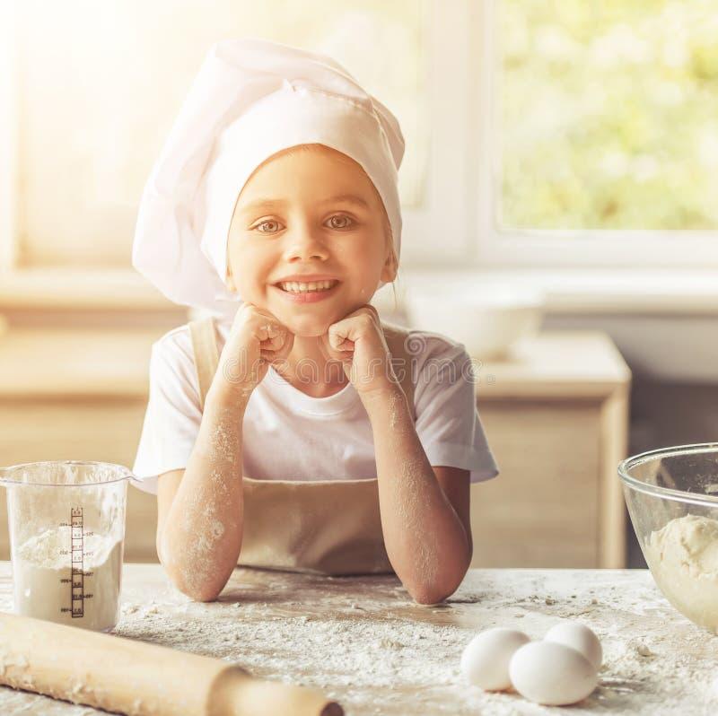 Bambina felice sveglia in grembiule e cuoco unico Hat fotografia stock libera da diritti