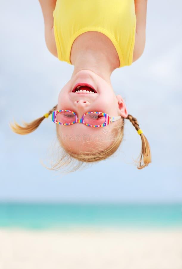 Bambina felice upside-down fotografia stock