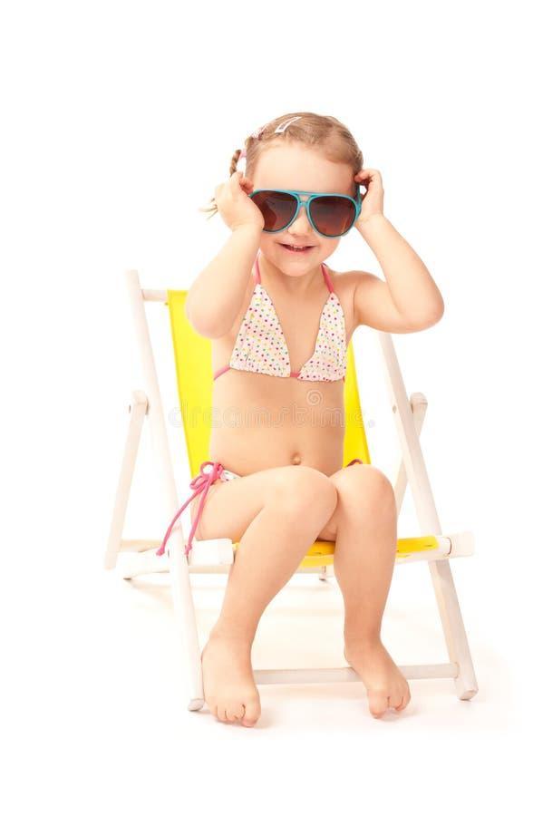 Bambina in grandi occhiali da sole che si siedono sul deckchair immagine stock libera da diritti