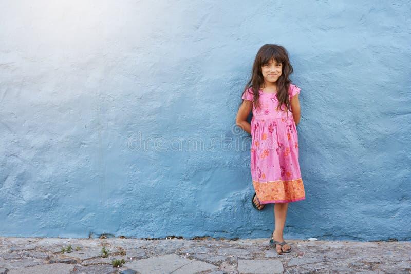 Bambina graziosa che esamina macchina fotografica e sorridere fotografie stock libere da diritti