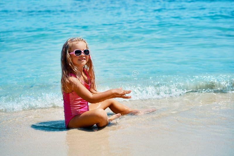 Bambina graziosa che gioca nel mare del turchese sulla bella spiaggia tropicale fotografia stock libera da diritti