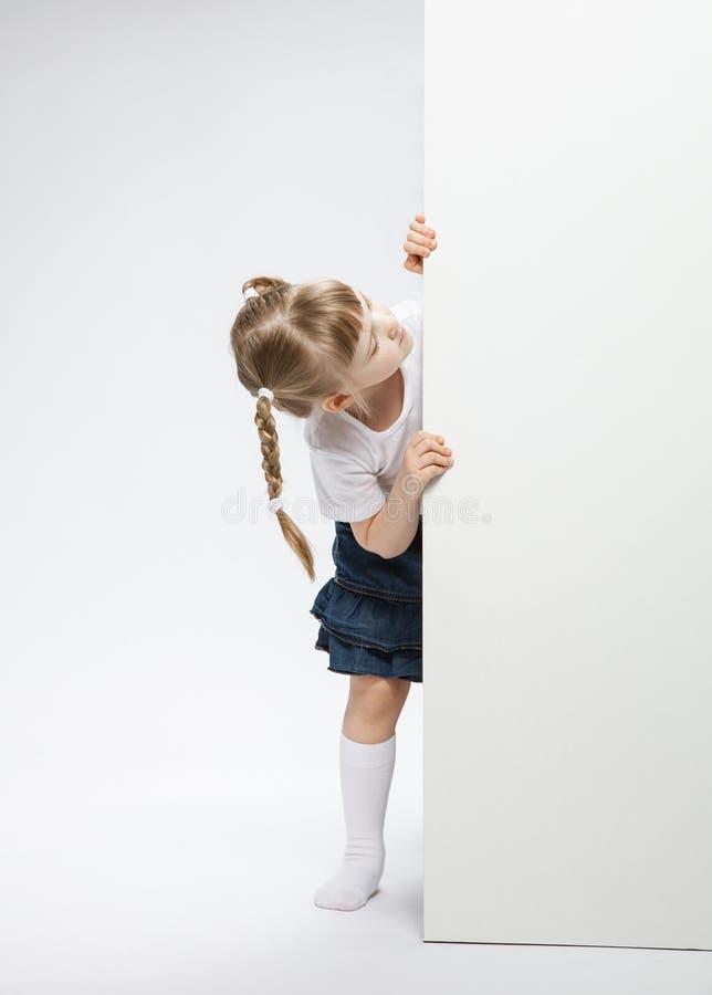 Bambina graziosa che guarda dalla porta immagine stock