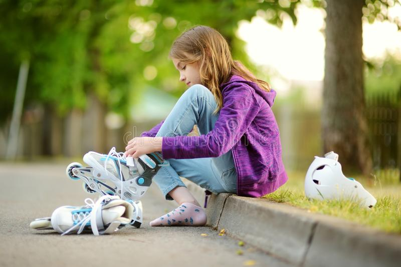 Bambina graziosa che impara al pattino di rullo il giorno di estate in un parco Casco di sicurezza d'uso del bambino che gode del fotografie stock