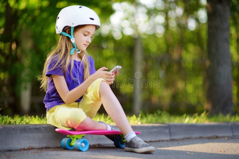 Bambina graziosa che impara pattinare il bello giorno di estate in un parco Bambino che gode del giro pattinante all'aperto fotografie stock libere da diritti