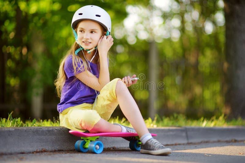 Bambina graziosa che impara pattinare il bello giorno di estate in un parco Bambino che gode del giro pattinante all'aperto fotografia stock