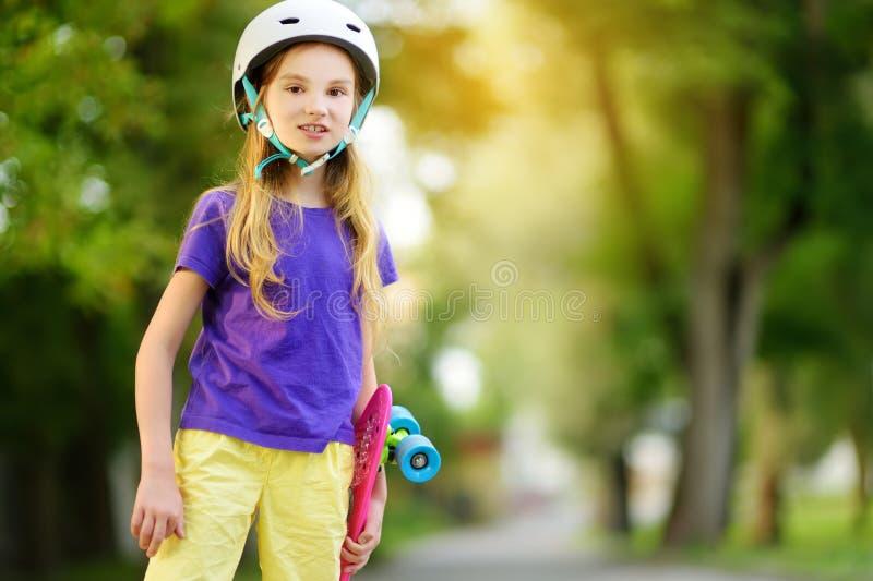 Bambina graziosa che impara pattinare il bello giorno di estate in un parco Bambino che gode del giro pattinante all'aperto fotografia stock libera da diritti