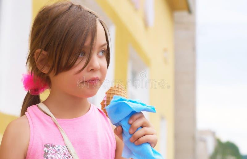 Bambina graziosa che mangia leccando il grande gelato nella risata felice del cono delle cialde sul fondo della natura fotografie stock libere da diritti