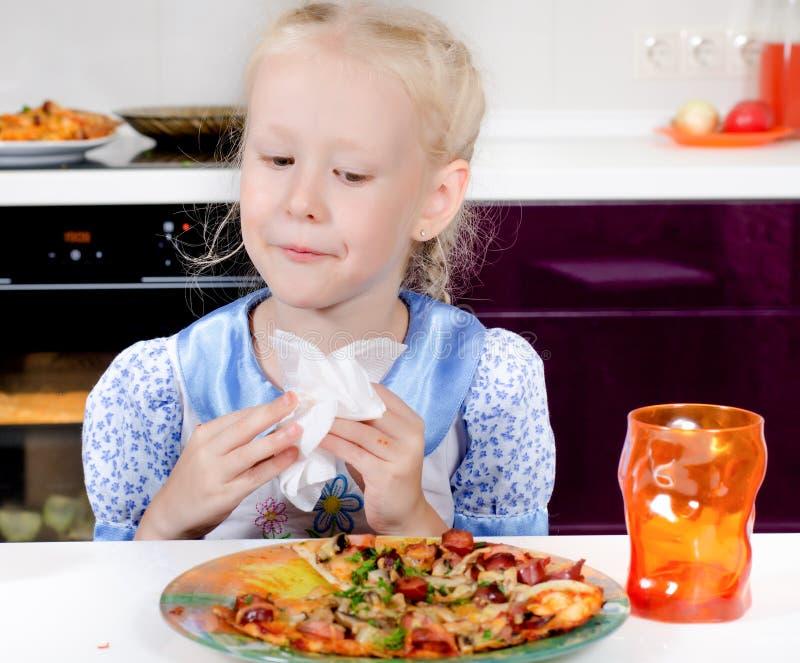 Bambina graziosa che mangia pizza casalinga immagini stock