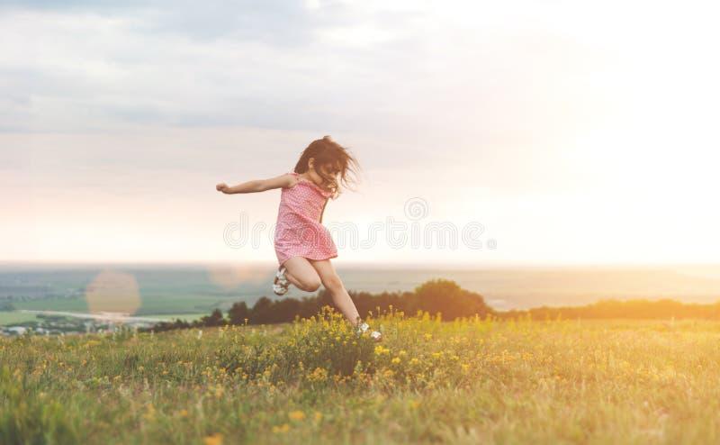 Bambina graziosa che salta all'aperto immagini stock