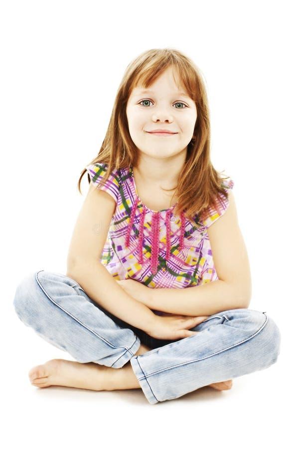 Bambina graziosa che si siede sul pavimento in jeans immagine stock