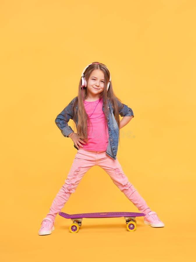 Bambina graziosa che sta sul fondo giallo immagini stock libere da diritti