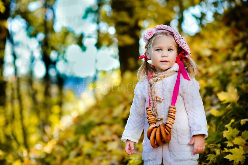 Bambina graziosa con i bagel nella sosta di autunno fotografia stock