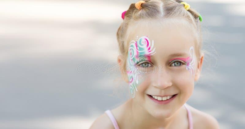 Bambina graziosa con il fronte dipinto fotografia stock libera da diritti