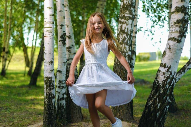 Bambina graziosa nei giri rapidi e nei balli bianchi del vestito fra gli alberi immagini stock libere da diritti