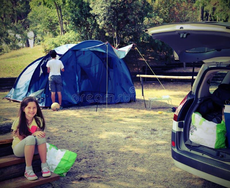 Bambina graziosa nel campeggio con la tenda ed suo fratello con fotografie stock