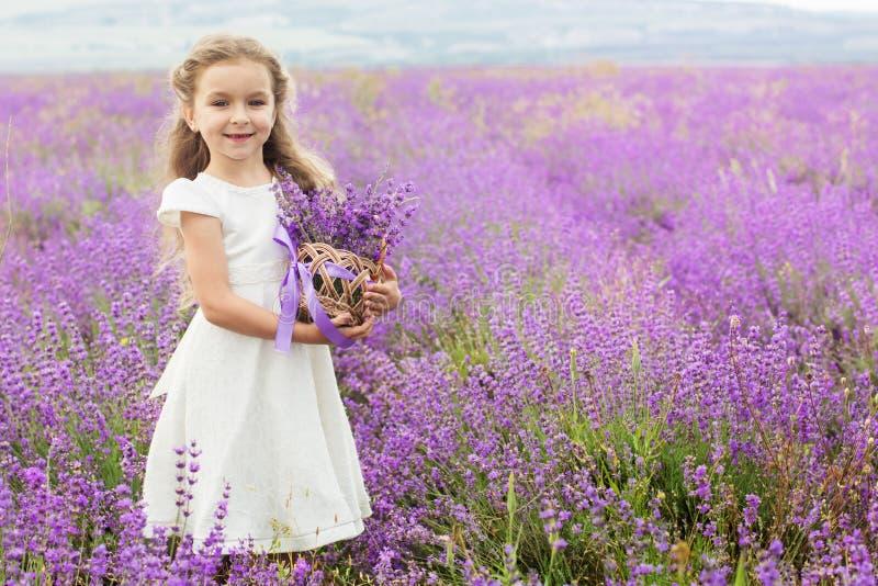 Bambina graziosa nel giacimento della lavanda con il canestro fotografie stock libere da diritti