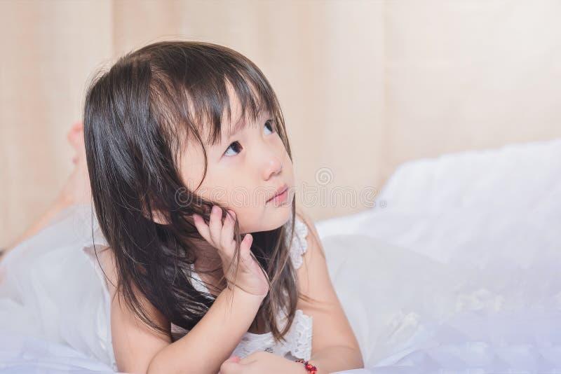 Bambina graziosa sul letto che si alza dal suo sonno e che pensa appena a cui ` farà per divertimento durante fotografia stock libera da diritti