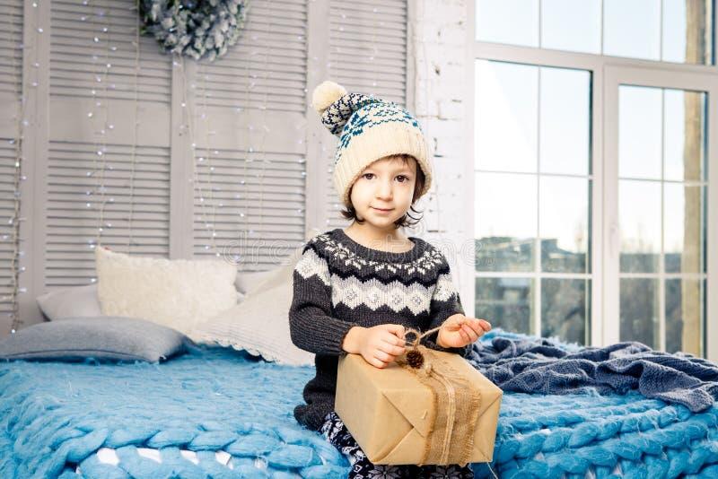 Bambina il bambino che si siede in pigiami e cappello sul letto con la ghirlanda delle lampadine con i contenitori di regali avvo immagini stock libere da diritti
