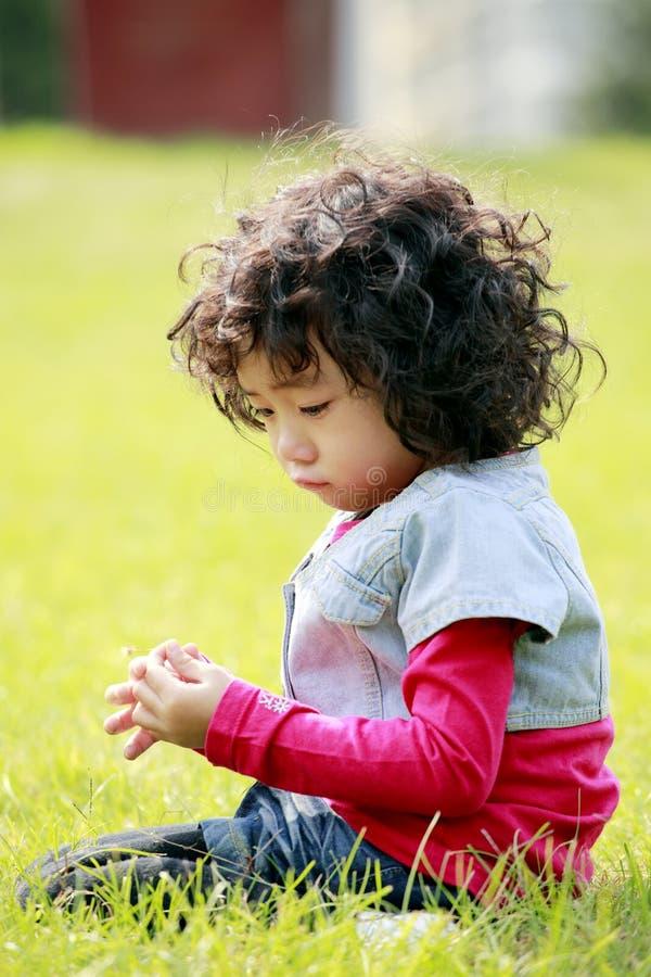 Bambina infelice sull'erba fotografia stock