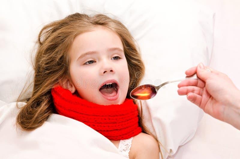 Bambina a letto che prende medicina con il cucchiaio fotografia stock