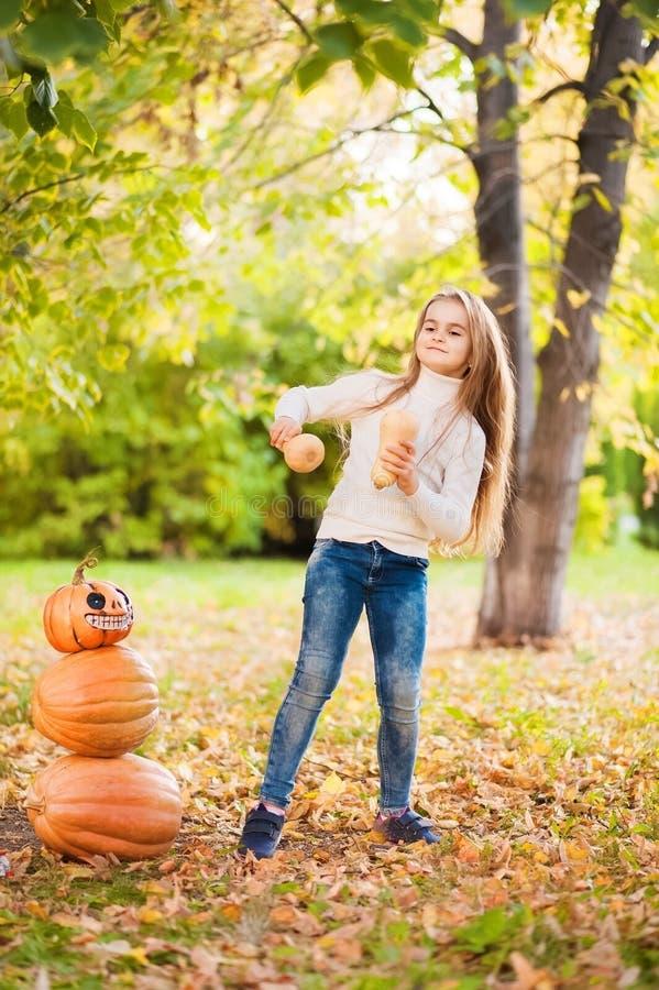 Bambina in maglione bianco e jeans su un fondo di sfondo naturale strutturale verde Una ragazza che balla con le zucche vicino al fotografia stock libera da diritti