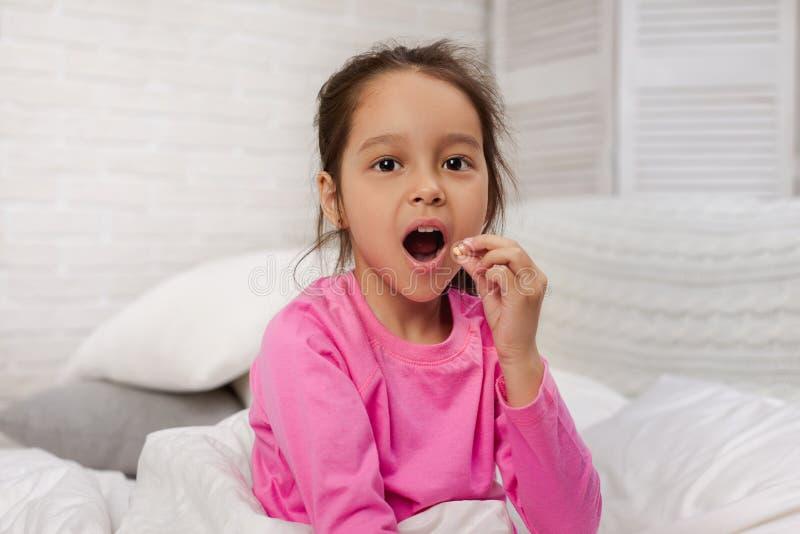 Bambina malata che si trova a letto fotografia stock
