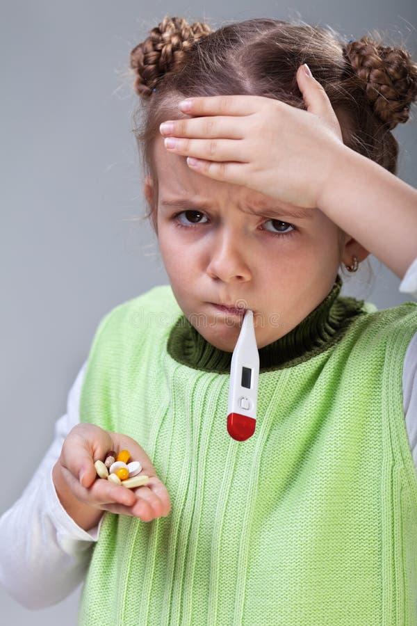 Bambina malata con le pillole ed il termometro immagine stock