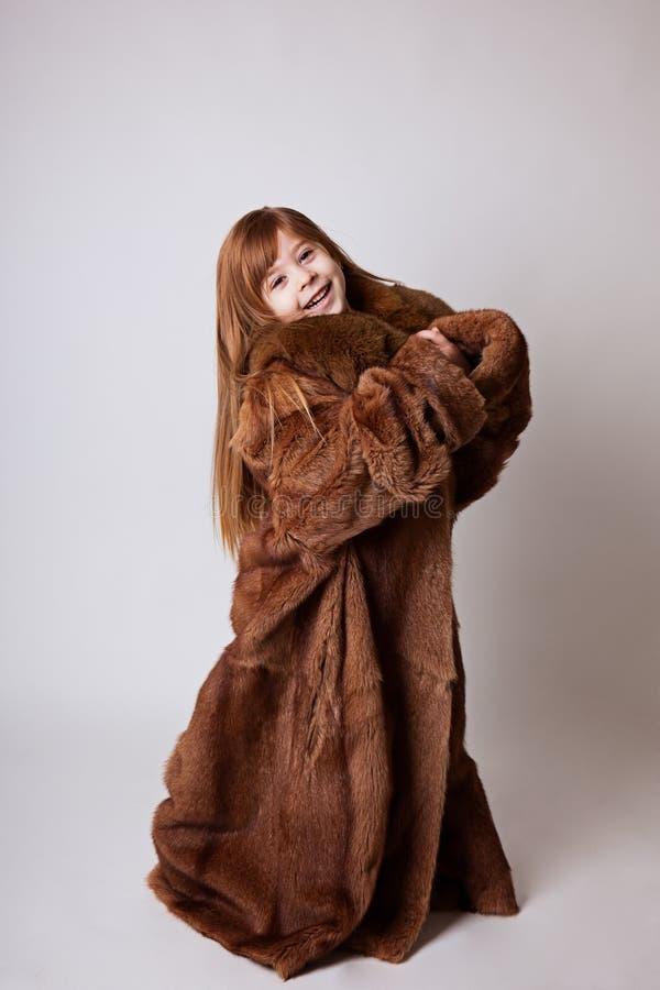 Bambina in mio cappotto lungo marrone del ` s della madre fotografia stock