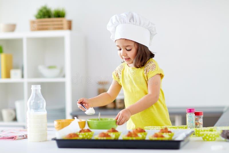 Bambina in muffin di cottura del toque dei cuochi unici a casa immagine stock libera da diritti