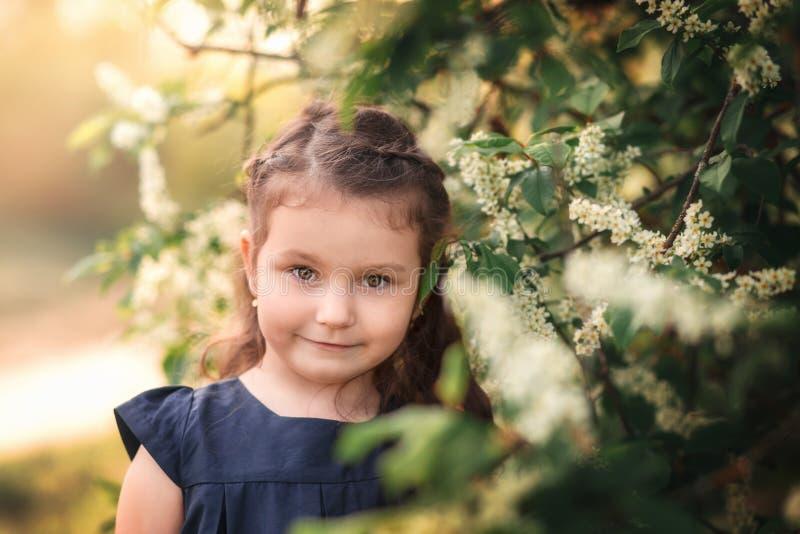Bambina nel giardino con gli alberi di fioritura immagini stock