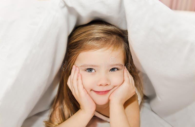 Bambina nel letto nell'ambito del coperchio immagini stock libere da diritti