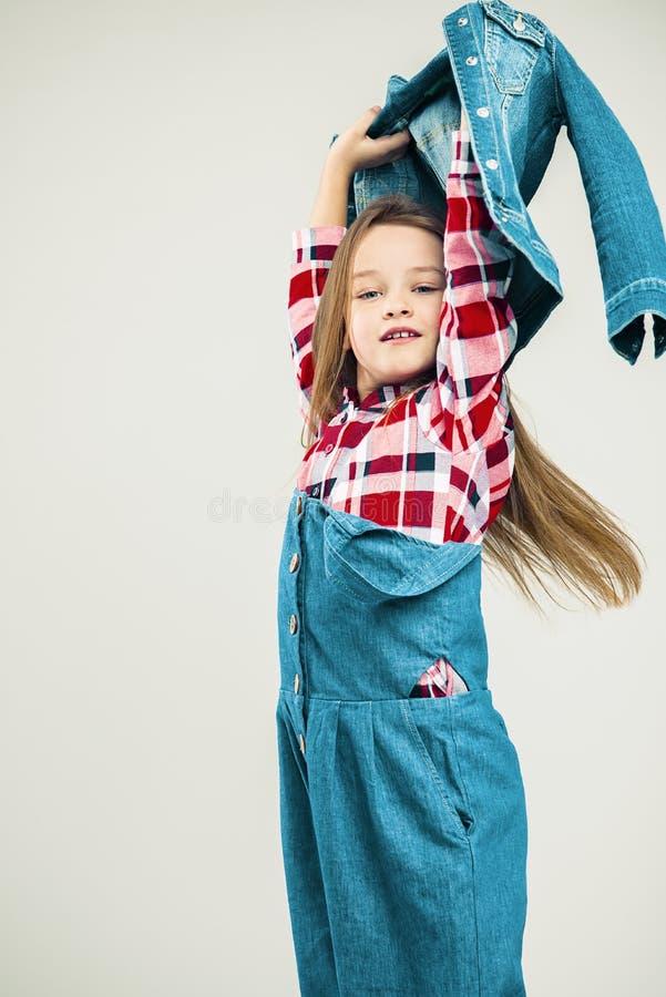 Bambina nel moto bambino con l'acconciatura dell'aria Bambino nel vestito del denim e camicia di plaid che posa nello studio Foto immagini stock